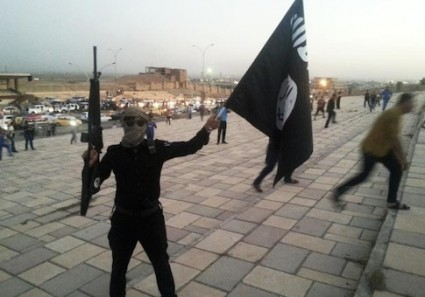 A fighter of the Islamic State of Iraq and the Levant (ISIL) holds an ISIL flag and a weapon on a street in the city of Mosul