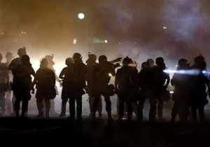 police walk through a cloud of smoke as they clash with protesters in Ferguson, Mo.