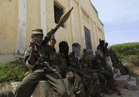 Al Shabaab soldiers sit outside a building during patrol