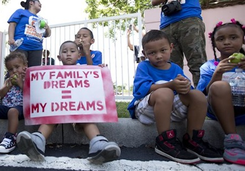 Kids sit on the sidewalk during an immigration rally in Deerfield Beach, Fla., Wednesday, Aug. 14, 2014