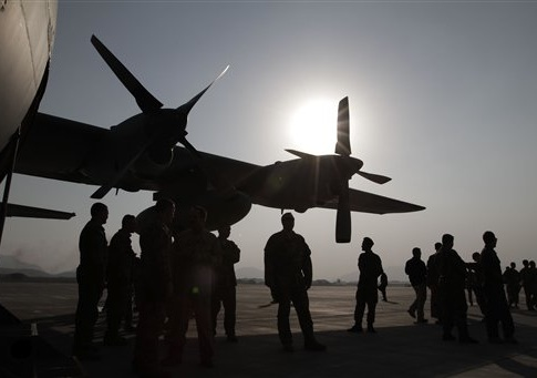 Afghan National Army and International Security Assistance Force personnel gather near a C-130 transport aircraft during a handover ceremony at the Afghan Air Force Base in Kabul