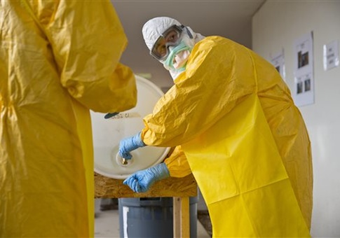 A licensed clinician sanitizes his hands after a simulated Ebola training session