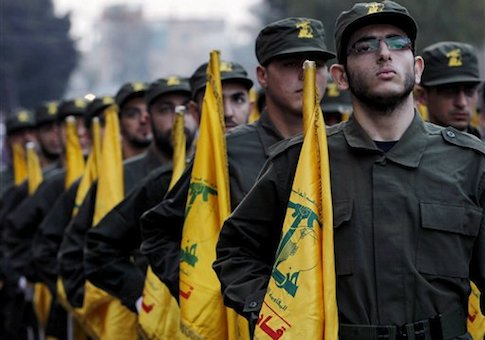 Hezbollah fighters hold their party flags