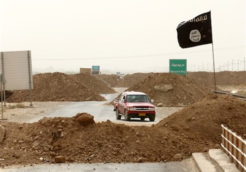 Islamic State militants pass a checkpoint bearing the group's trademark black flag in the village of Maryam Begg in Kirkuk, 290 kilometers (180 miles) north of Baghdad, Iraq