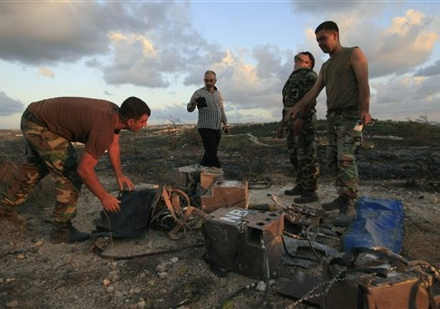 Lebanese army soldiers inspect what they say are destroyed parts of an Israeli spying device planted in Adloun village, south Lebanon, on Friday Sept. 5, 2014. Israel remotely detonated a spying device planted in south Lebanon