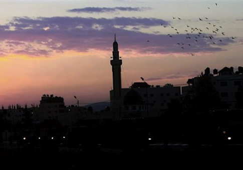 Birds fly over a mosque at the sunrise in the West Bank refugee camp of Jenin early, Thursday, Oct. 2