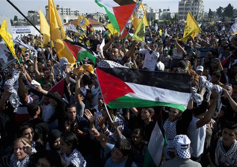 Palestinian supporters fly Palestinian and Fatah party flags, chant slogans and dance during a ceremony marking the 10th anniversary of the late Palestinian leader Yasser Arafat's death, at the Palestinian Authority headquarters, in the West Bank city of Ramallah