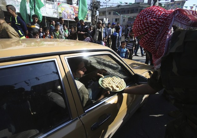 A masked Palestinian distributes sweets as he celebrates with others an attack on a Jerusalem synagogue, in Rafah in the southern Gaza Strip