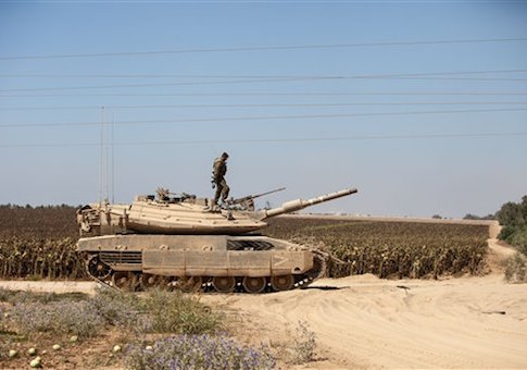 An Israeli soldier is standing on the top of a tank, near the border with Gaza