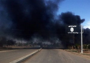 Smoke billows behind an Islamic State group sign