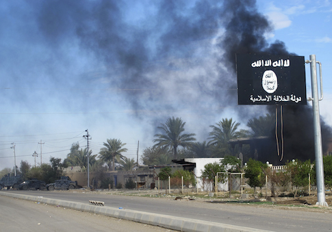 Smoke raises behind an Islamic State flag after Iraqi security forces and Shiite fighters took control of Saadiya in Diyala province from Islamist State militants