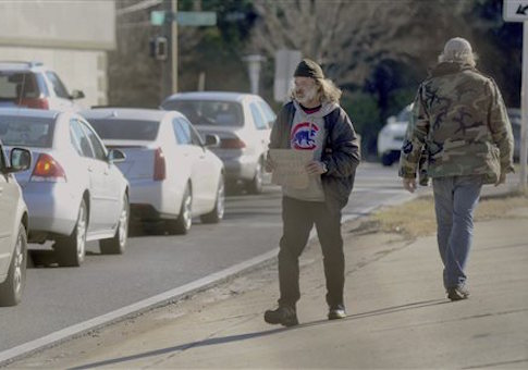 Homeless veteran Michael Wilson holds a sign up in front of traffic on Tuesday, Jan. 21,2014, in Fort Walton Beach, Fla.