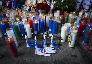 Candles and other items left by visitors make up a growing makeshift memorial Tuesday, Dec. 23, 2014, near the site where New York Police Department officers Rafael Ramos and Wenjian Liu were murdered in the Brooklyn borough of New York