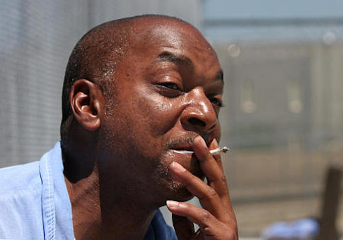 An inmate at a California state prison enjoys a hand-rolled cigarette in the prison's minimum security yard
