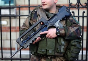 A French soldier helps secure the perimeter of a Jewish school in Paris as part of the highest level of security plan after last week's attacks by Islamist militants, Wednesday, Jan. 14