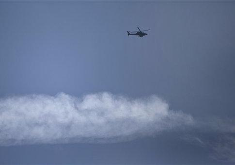 An Israeli helicopter flies over the Israel-Lebanon border, Wednesday, Jan. 28, 2015