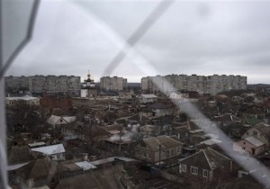 Smoke rises from a destroyed house, in foreground center, damaged in Saturday's shelling at Vostochniy district of Mariupol, Ukraine, Monday, Jan. 26, 2015