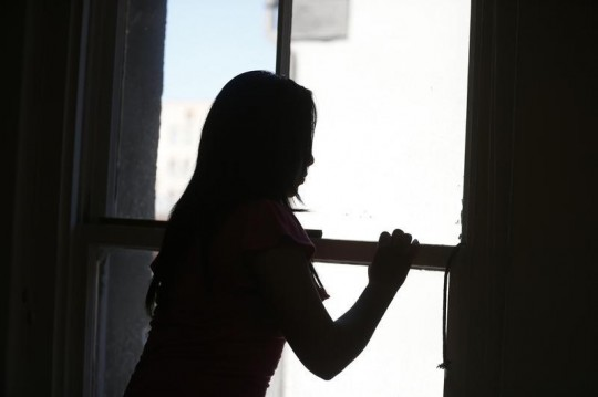 Maria, an undocumented migrant from Central America, looks out of a window in Los Angeles