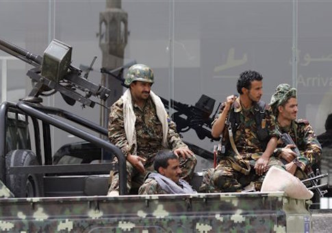 Shiite rebels, known as Houthis, wearing an army uniform, ride on an armed truck to patrol the international airport in Sanaa, Yemen
