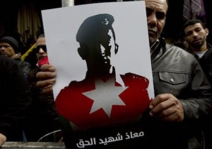 A Jordanian demonstrator carries a poster with a picture of slain Jordanian pilot, Lt. Muath al-Kaseasbeh