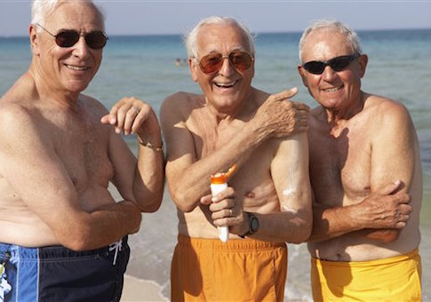 Senior men applying sunscreen on beach