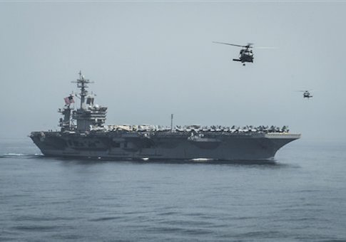 In this April 13, 2015 photo released by U.S. Navy Media Content Services, helicopters fly from the aircraft carrier USS Theodore Roosevelt during a vertical replenishment with the aircraft carrier USS Carl Vinson in the Gulf of Oman