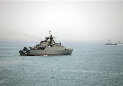 Iranian warship Alborz, foreground, prepares before leaving Iran's waters, at the Strait of Hormuz