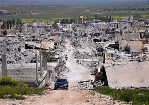 In this picture taken on Saturday, April 18, 2015, a car passes in an area that was destroyed during the battle between the U.S. backed Kurdish forces and the Islamic State fighters