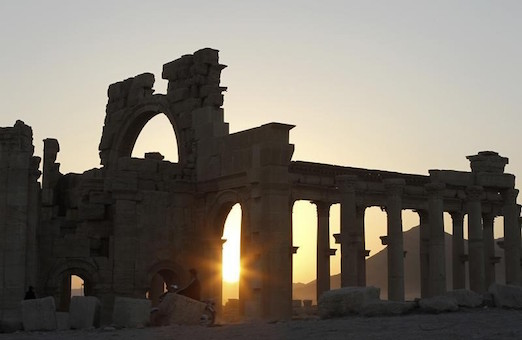 The sun sets behind ruined columns at the historical city of Palmyra, in the Syrian desert