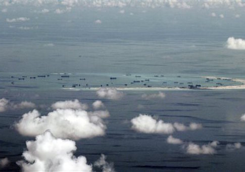 This areal photo taken through a glass window of a military plane shows China's alleged on-going reclamation of Mischief Reef in the Spratly Islands in the South China Sea Monday, May 11