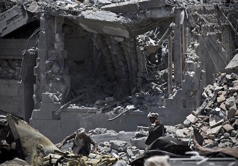 Shiite fighters, known as Houthis, collect ammunition at the residence of a military commander of the Houthi militant group, destroyed by a Saudi-led airstrike in Sanaa, Yemen, Tuesday, April 28