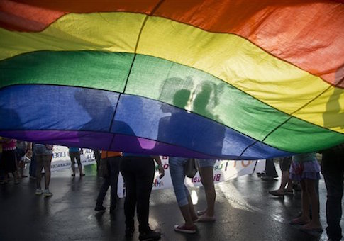 Members of the LGBT movement hold a gay pride flag as they attend a march to mark the International Day Against Homophobia in Managua, Nicaragua