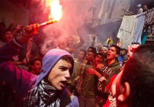 A youth carries a lit flare as supporters of the Muslim Brotherhood gather in the El-Mataria neighborhood of Cairo, Egypt on Friday, April 24, 2015