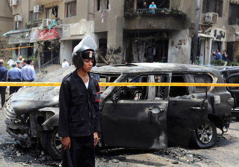 Policemen investigate the site of a car bomb attack on the convoy of Egyptian public prosecutor Hisham Barakat near his house at Heliopolis district in Cairo