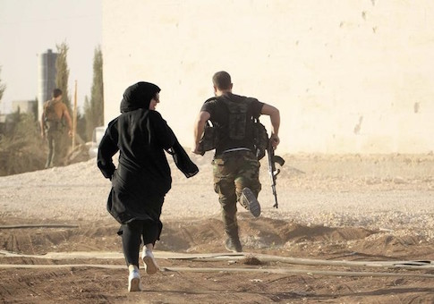A woman reporter runs with a rebel fighter to avoid snipers at the frontline against the Islamic State fighters in Aleppo's northern countryside