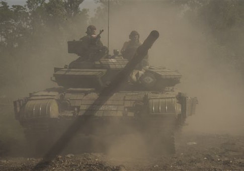 A Russia-backed rebel tank moves to position, near Donetsk airport, eastern Ukraine, Friday, June 12