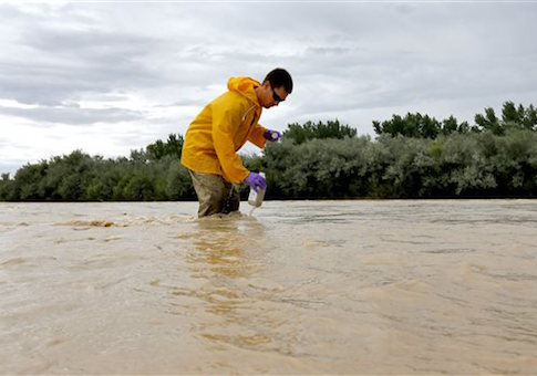 Hydrologic Technician Ryan Parker gathers water samples from the San Juan River