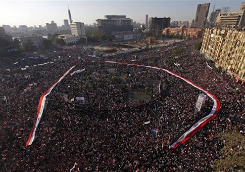 A long Egyptian flag is held by the crowd around Tahrir Square in Cairo, Egypt, Friday Feb. 18, 2011