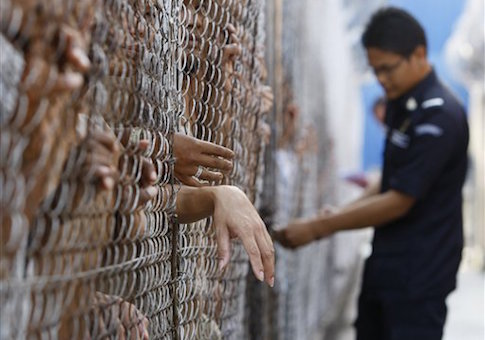 An immigration department guard locks a gate for detainees at the Lenggeng detention center, south of Kuala Lumpur, Malaysia