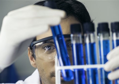 Researcher scrutinizing test tubes in laboratory (PhotoAlto via AP Images)