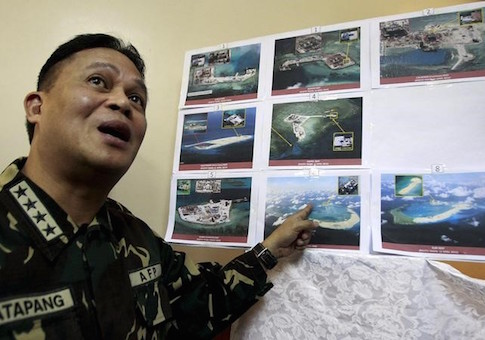 Armed Forces of the Philippines (AFP) Chief of Staff Gregorio Pio Catapang shows some images of the structures being built by China at the disputed islands during a news conference at the AFP headquarters in Manila April 20, 2015