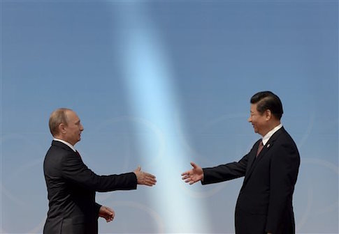 Russian President Vladimir Putin, left, is greeted by Chinese President Xi Jinping