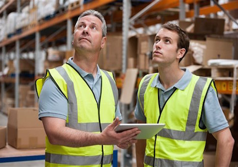 Men in warehouse using digital tablet