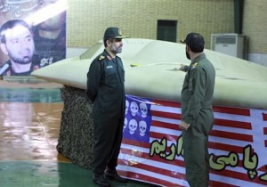 The chief of the aerospace division of Iran's Revolutionary Guards, Gen. Amir Ali Hajizadeh, left, listens to an unidentified colonel as he points to US RQ-170 Sentinel drone