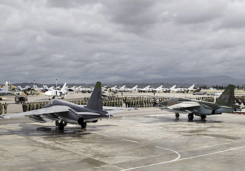 Russian and Syrian servicemen line up near military jets during a ceremony dedicated to the withdrawal of Russian troops from Syria