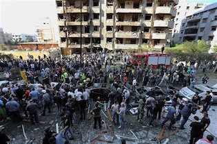 In this file photo taken Tuesday, Nov. 19, 2013, Lebanese people gather at the scene of an attack claimed by the Abdullah Azzam Brigades