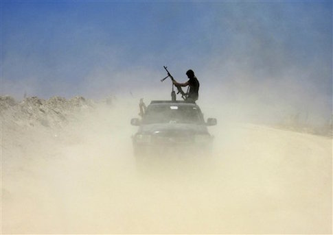 A fighter with Badr Brigades an armed Shiite group under the umbrella of the Popular Mobilization Forces loads his rifle as Iraqi security forces and allied Shiite Popular Mobilization Forces and Sunni tribal fighters, take combat positions outside Fallujah / AP