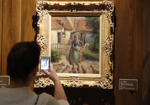 A visitor takes a photograph of a painting called 'Shepherdess Bringing in Sheep' that the Nazis stole / AP
