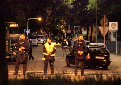 Police stand in a small street following a shooting rampage at the Olympia shopping mall in Munich