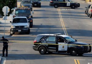 San Diego police officers investigate the scene where an officer was fatally shot and another was injured at a traffic stop late on Thursday, in San Diego